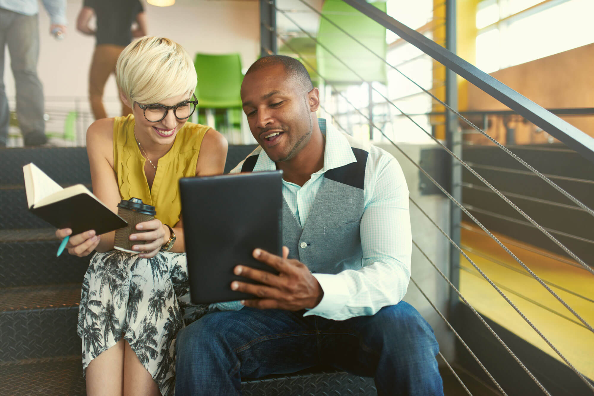 Photo of Two People sitting on a Staircase looking at a Tablet