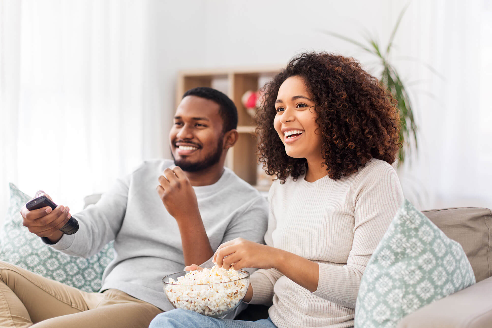 Photo of Man and Woman sitting on Couch with Bowl of Popcorn