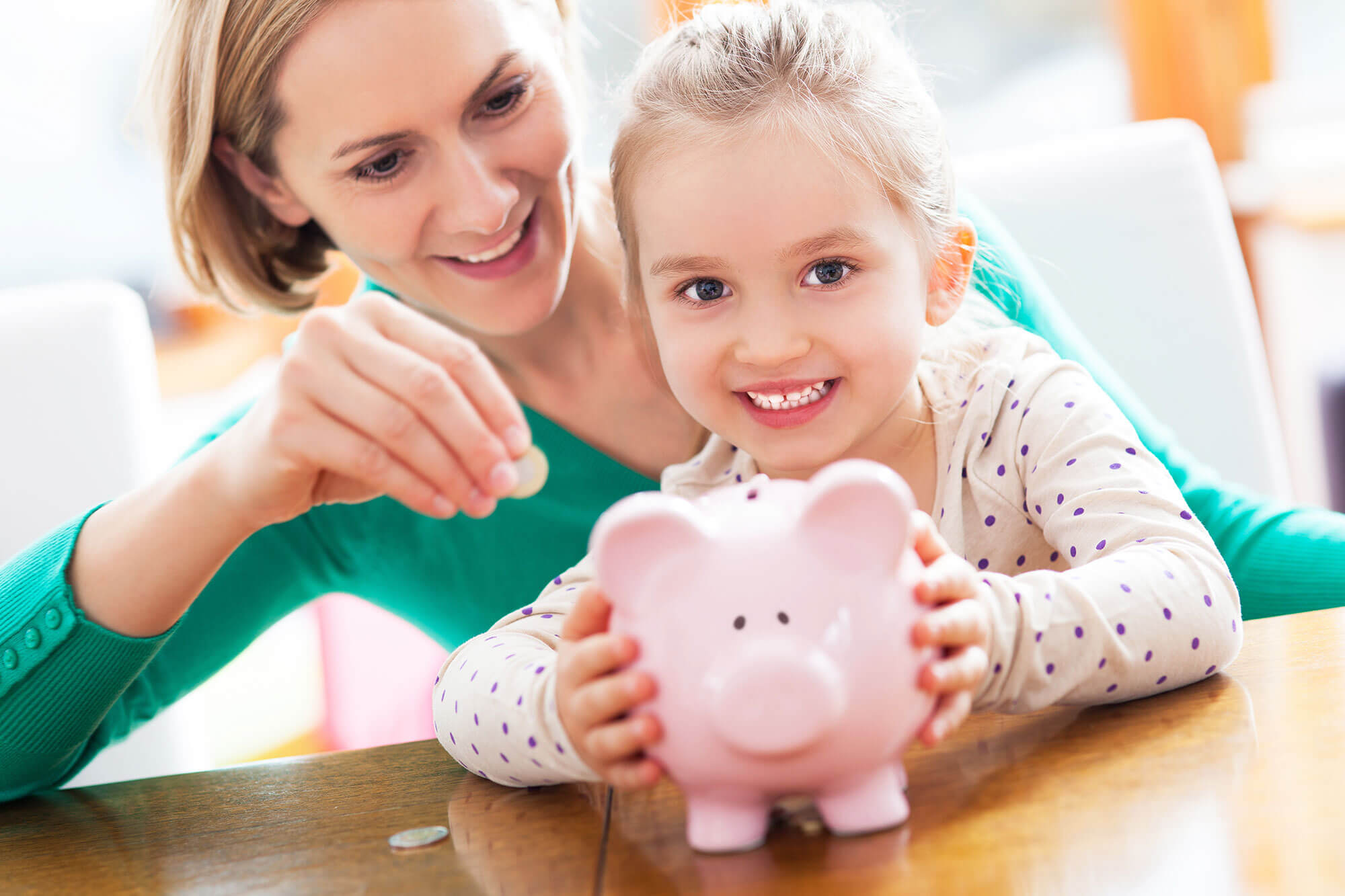 Photo of a Small Child and Woman putting coins into a Piggy Bank