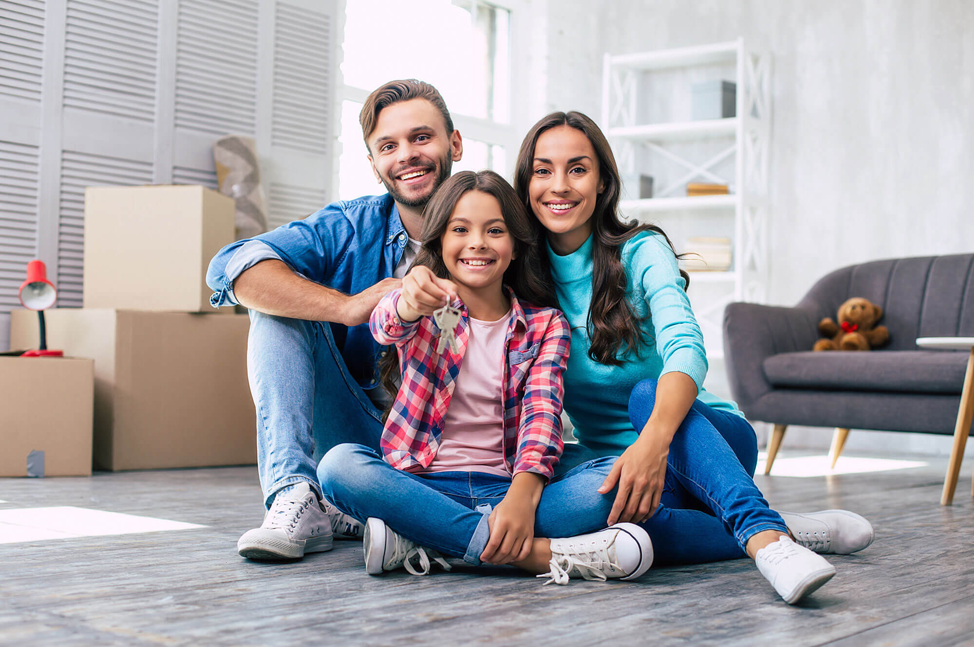 Photo of a Small Family sitting in front of Boxes holding Keys