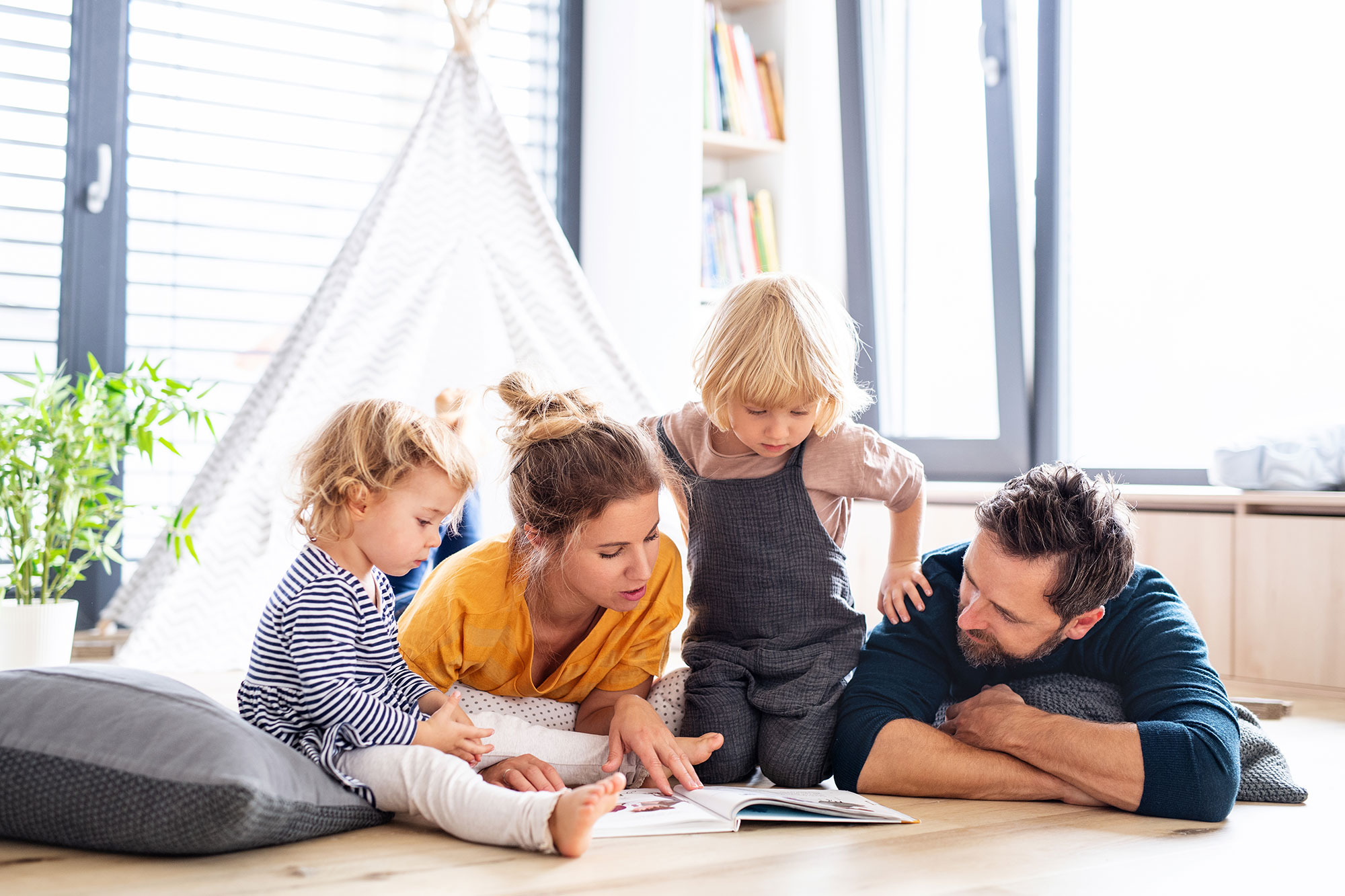 Photo of Small Family laying on floor reading a book